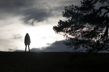 female silhouette standing on the top of hill