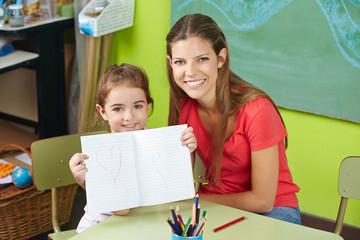 Stolzes Kind zeigt Zeichnung im Kindergarten