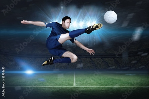 Composite image of football player in blue kicking