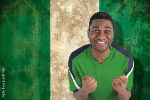 Composite image of cheering football fan in green jersey