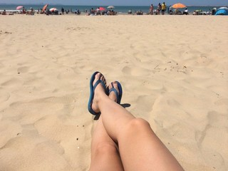Girl legs and shoes at the beach