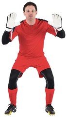 Goalkeeper in red ready to catch
