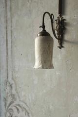 Alte Lampe an einer Wand mit Fresken