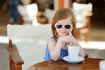 A girl drinking hot chocolate in outdoor cafe