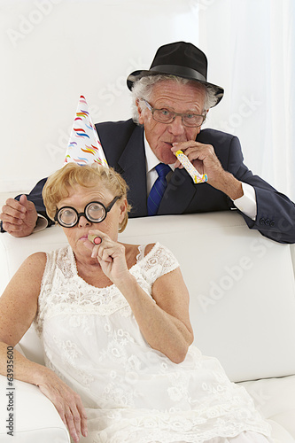 Senior couple sitting on couch wearing party hats celebrating