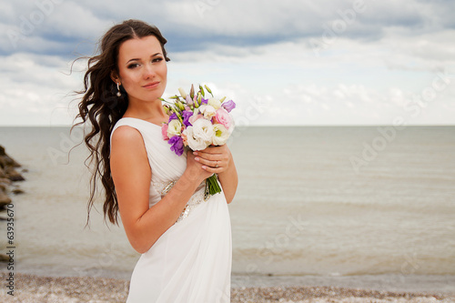 Gentle bride with a bouquet on the beach.
