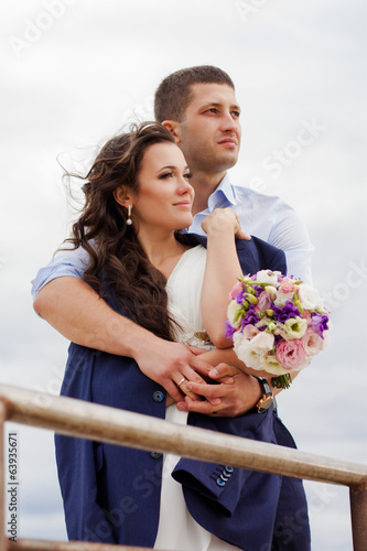 Loving bride and groom standing on the pier