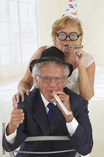 funny elderly couple in festivity blowing and making noise