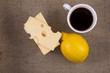 Cup of coffee with lemon and cheese on the burlap