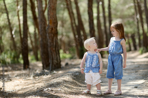 Two little sisters outdoors at summer day