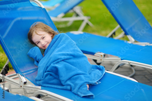 Girl covered with a towel sitting near pool