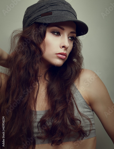 Sexy female model posing in modern cap. Vintage portrait