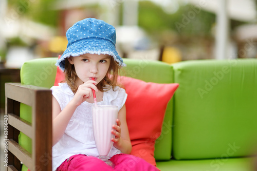 A girl drinking milkshake in outdoor restaurant