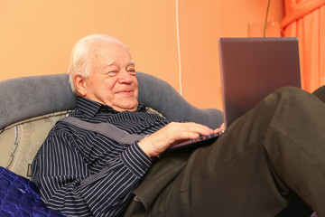 Old man with notebook lying on the bed