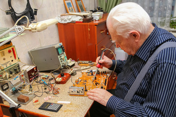 Old engineer works at his home laboratory
