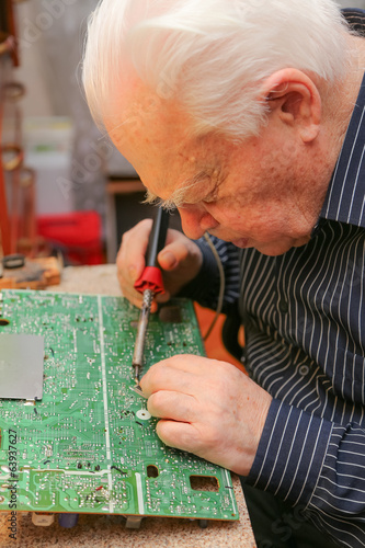 Old man works at his home laboratory