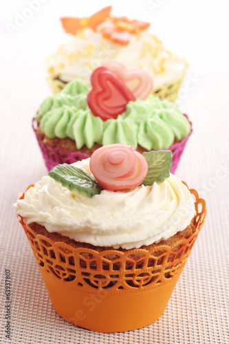 Three cupcakes with marzipan decorations.