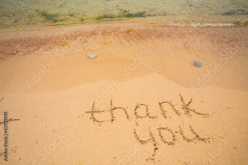 Thank you written in the sand on beach.