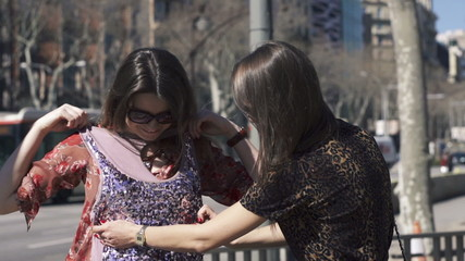Girlfriends checking clothes in the city, super slow motion