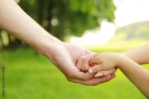Family parents hold the hand of a small child