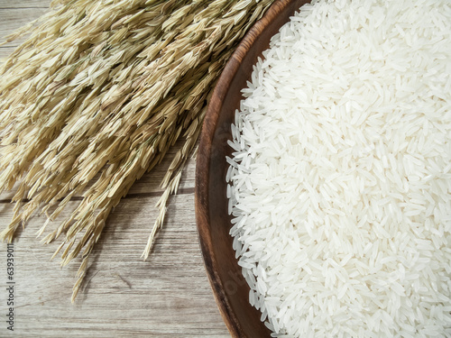 white rice on the wooden plate and rice plant