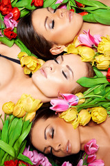 Three beautiful sensual women with colorful tulips