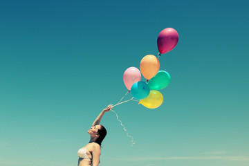 Young redhead woman holding balloons