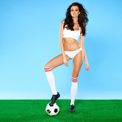 Beautiful curvy brunette posing with a soccer ball