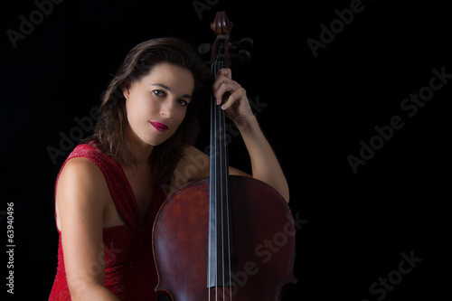 Beautiful brunette playing cello with selective light in red dre