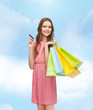 smiling woman in dress with many shopping bags