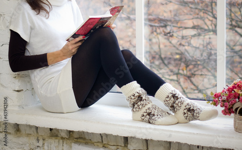 Girl holding book and looking through window