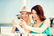 canvas print picture - girls taking photo in cafe on the beach