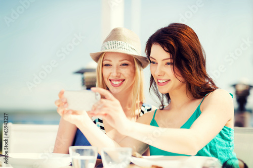 canvas print picture girls taking photo in cafe on the beach