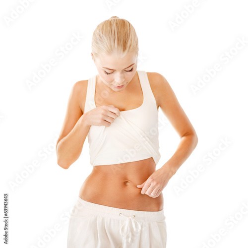 fit woman measuring fat level on her belly