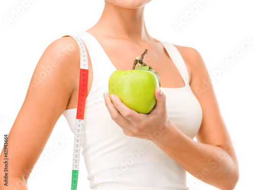 female hand with apple and measuring tape