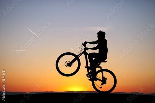 silhouette of boy riding his mountain-bike in sunset