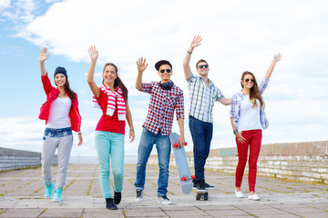 group of smiling teenagers waving hands