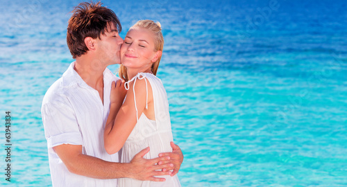 Happy couple kissing on the beach