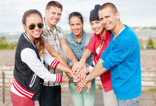 teenagers hands on top of each other outdoors