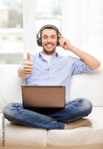 smiling man with laptop and headphones at home