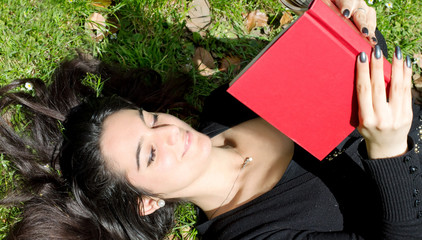 beautiful girl during a funny reading lying on a garden