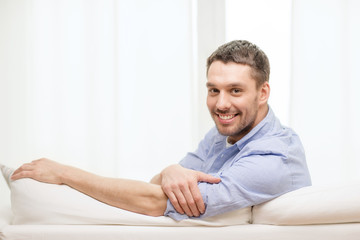 smiling man sitting on sofa at home