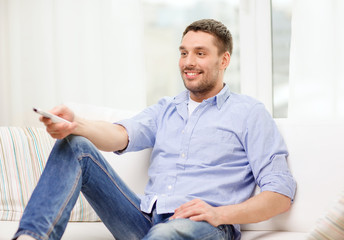 smiling man with tv remote control at home