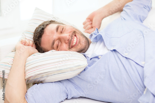 smiling young man lying on sofa at home