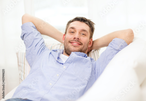 smiling man lying on sofa at home