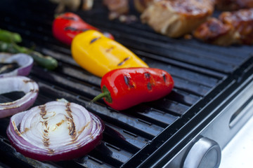 Peppers and onions and Barbecue Pork cooking on a grill.