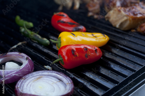 Peppers and onions and Barbecue Pork cooking on a grill