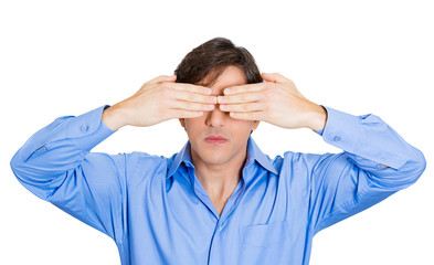See no evil concept. Man covers eyes doesn't want to see