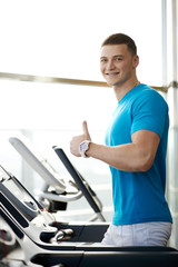man showing thumbs up near the treadmill