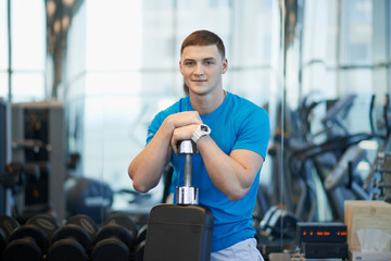 man sits leaning on a dumbbell